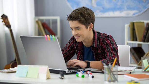 lächelnde teen männlich chatten mit freunden in sozialen netzwerken sitzen vor laptop - jugendalter stock-fotos und bilder
