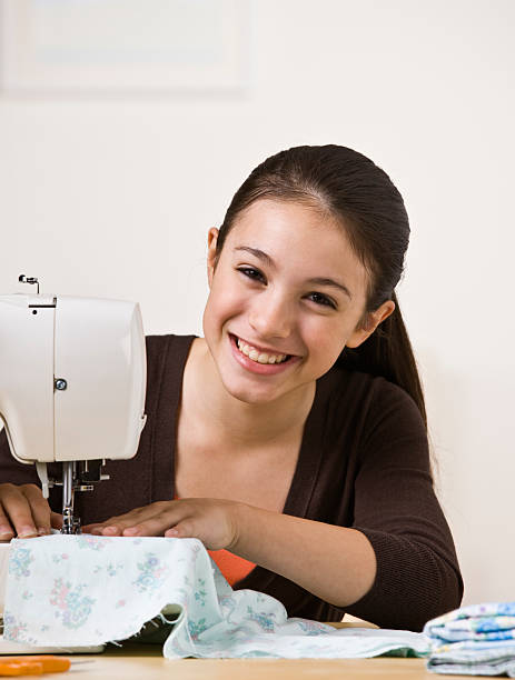Smiling Teen Sewing stock photo