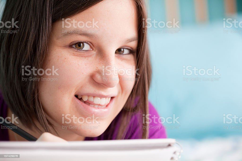 Smiling teen writing on her bed royalty-free stock photo