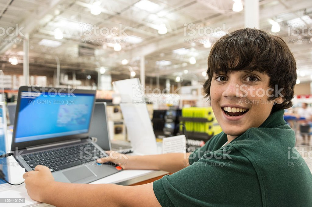 Smiling teenage boy choosing a lap top stock photo