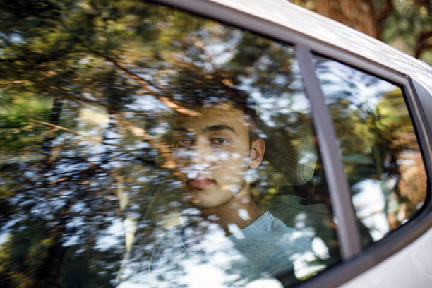 Smiling teenage boy in the car Smiling teenage boy in the car boy looking out window stock pictures, royalty-free photos & images