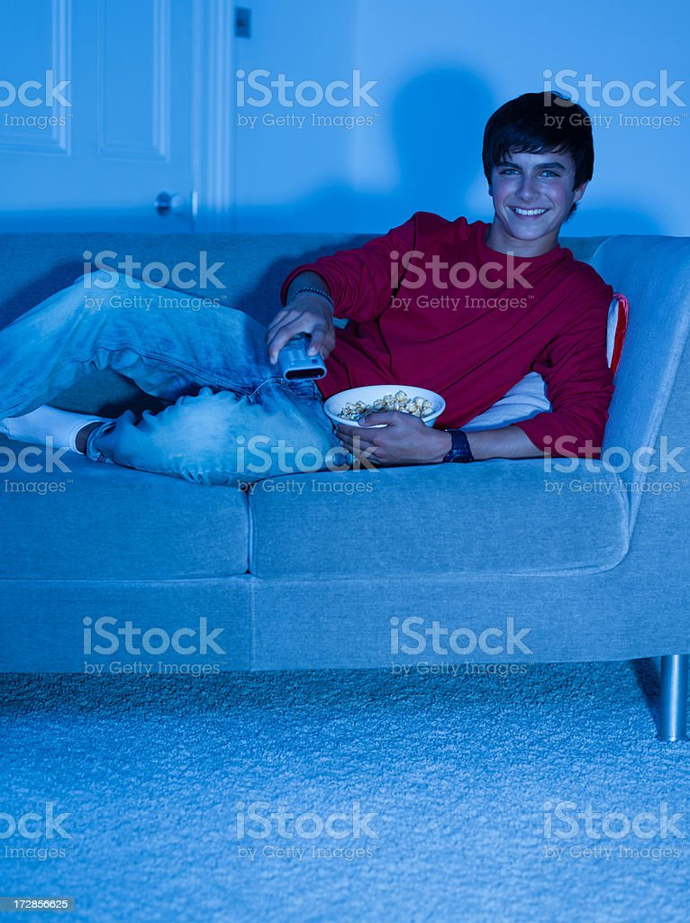 Smiling teenage boy laying on sofa with remote control royalty-free stock photo