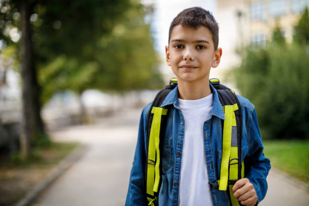 Smiling teenage boy with school bag in front of school stock photo