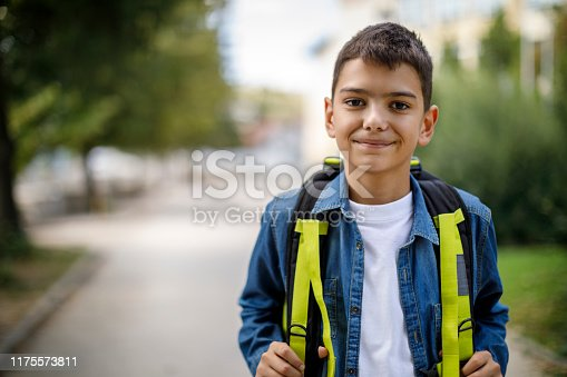 Smiling teenage boy with school bag in front of school