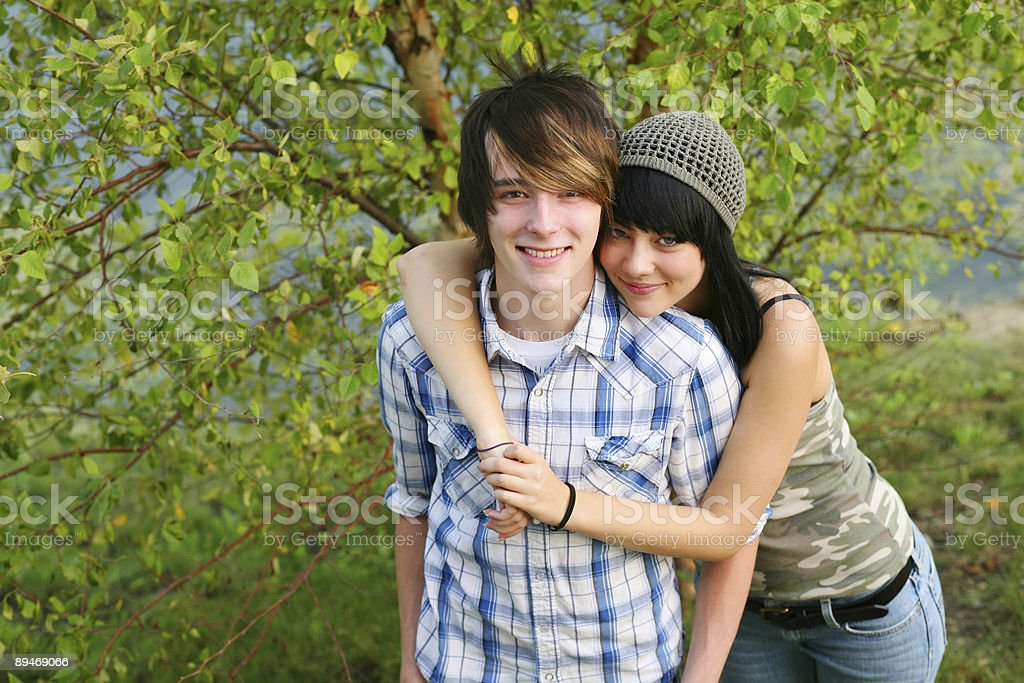 Smiling teenage couple with the girl's arms around the boy stock photo