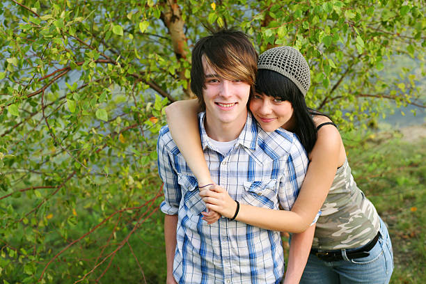 Smiling teenage couple with the girl's arms around the boy attractive teen guy and girl outside cute teen couple stock pictures, royalty-free photos & images