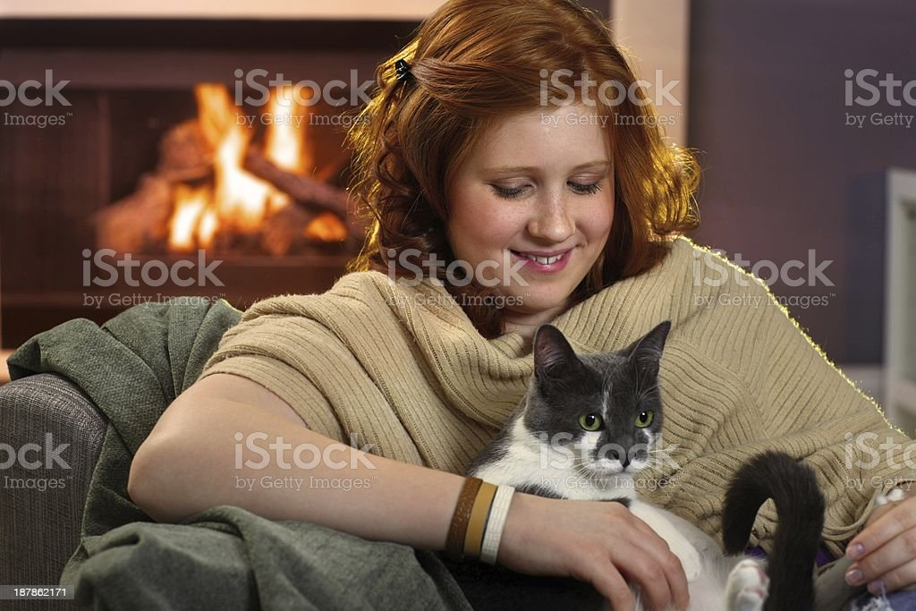 Smiling teenage girl loving her cat at home stock photo