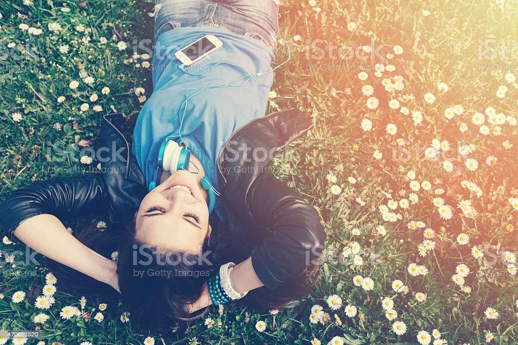 Smiling teenage girl lying on grass stock photo