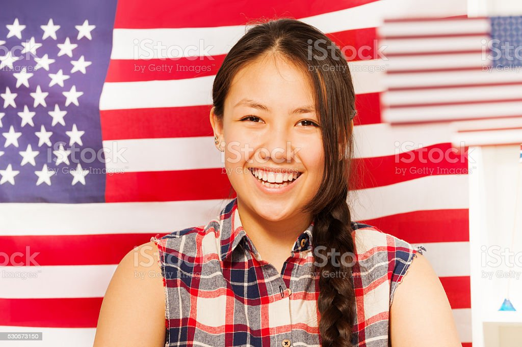 Smiling teenage girl with American flag behind her stock photo