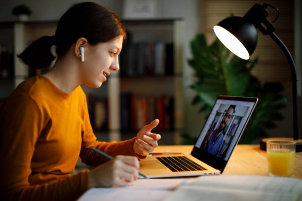 Smiling teenage girl with bluetooth headphones having video call on laptop computer at home stock photo