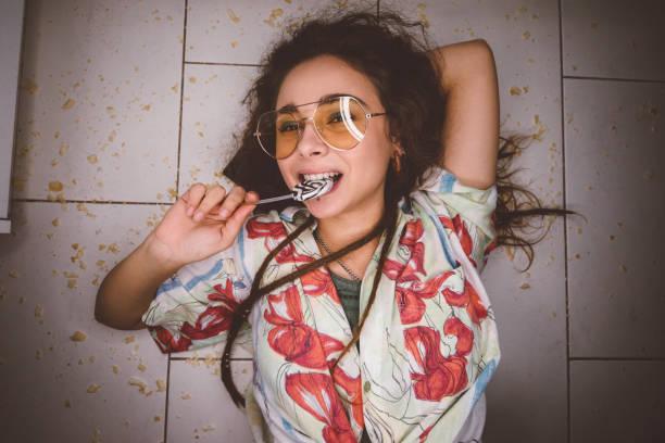 lächelnde teenager-mädchen mit lollipop auf schmutzigen boden liegend - anti unordnung stock-fotos und bilder