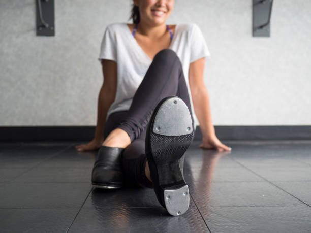 Smiling teenage tap dancer sitting cross legged in dance class relaxing stock photo