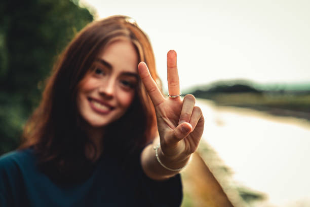 Smiling Teenage Woman Peace Handsign Outdoors in Sunset Light stock photo