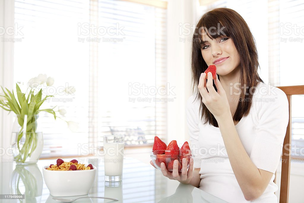 Smiling teenager eating a healthy breakfast royalty-free stock photo