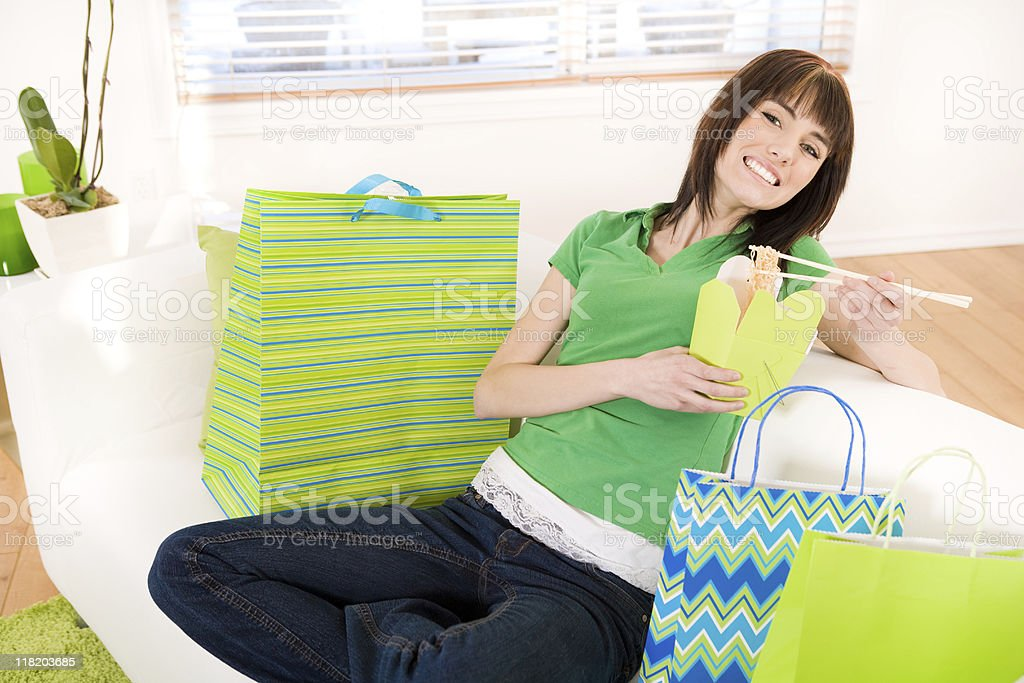 Smiling teenager eating chinese food with shopping bags royalty-free stock photo