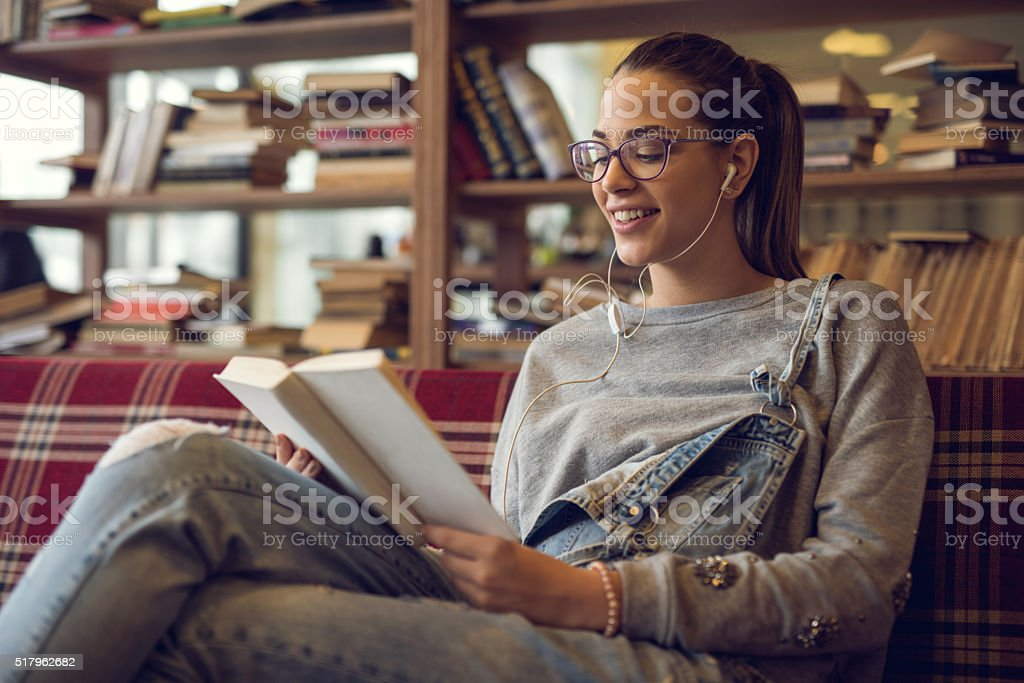 Smiling teenager enjoying in a music while reading a book. stock photo