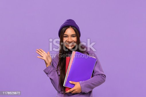 Smiling teenager student in a hat and sweater holding folders standing isolated over purple background. Concept of education