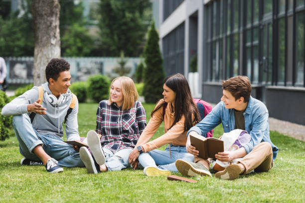 smiling teenagers sitting on grass, talking and holding books smiling teenagers sitting on grass, talking and holding books teenagers only stock pictures, royalty-free photos & images