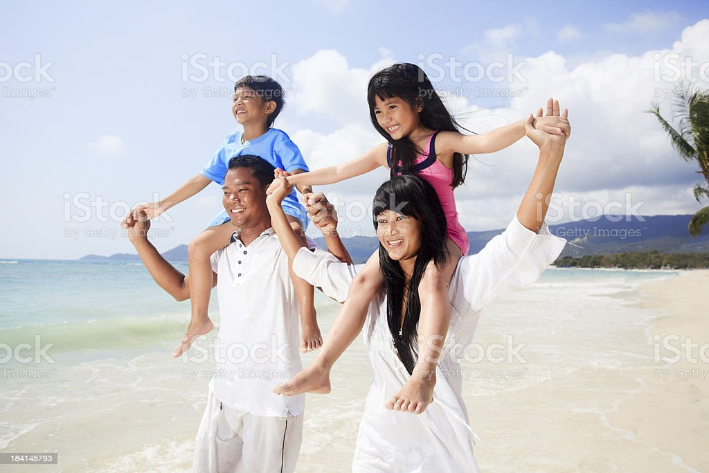 Smiling Thai family walking on the beach. royalty-free stock photo