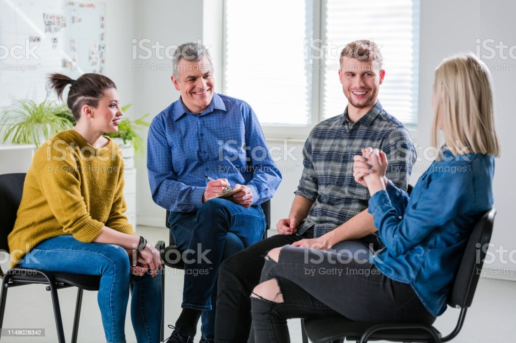 Smiling therapist and students looking at woman Smiling therapist and students looking at young woman in lecture hall. Female and male are sitting at university. They are in group therapy session. 18-19 Years Stock Photo