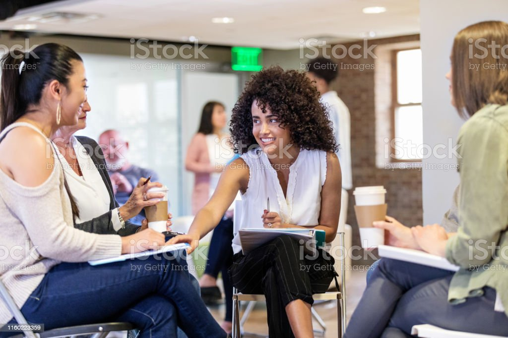 Caring young female therapist smiles while encouraging a woman during...