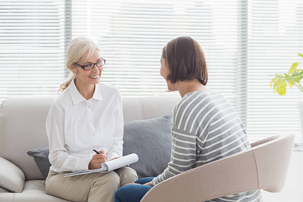smiling therapist with patient - psychiatrist stock photos and pictures