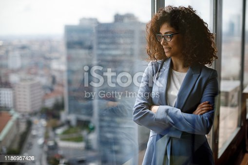 Smiling thoughtful businesswoman looking through window