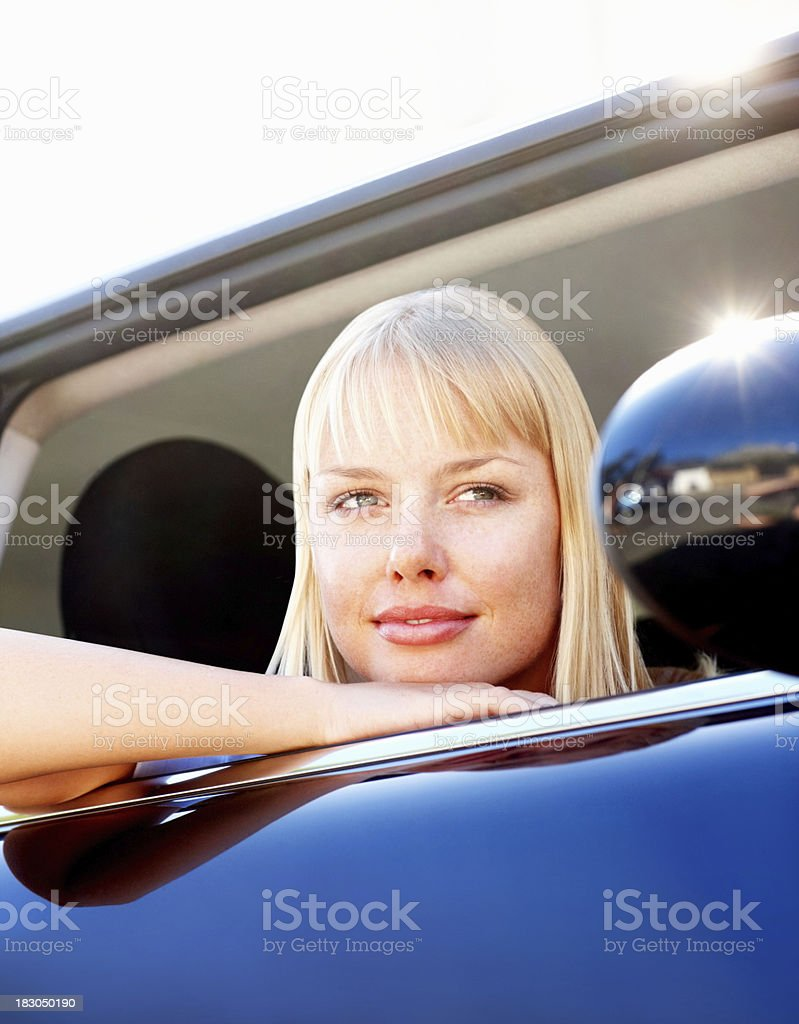 Smiling thoughtful female with head out of a car royalty-free stock photo
