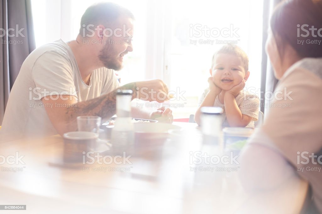 Smiling toddler having family meal time stock photo