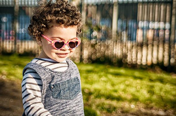 personen: lächelnd kleinkind (2-3) in spielplatz - sonnenbrille kleinkind stock-fotos und bilder