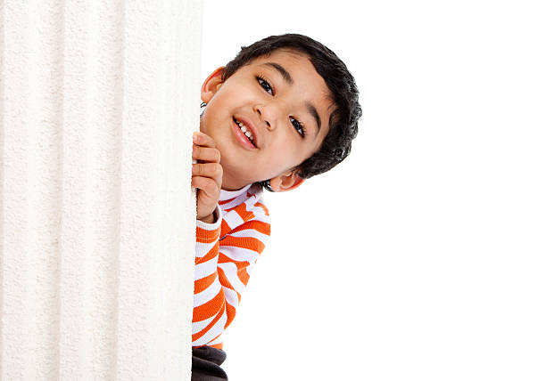 Smiling Toddler Peeks from Behind a Column stock photo