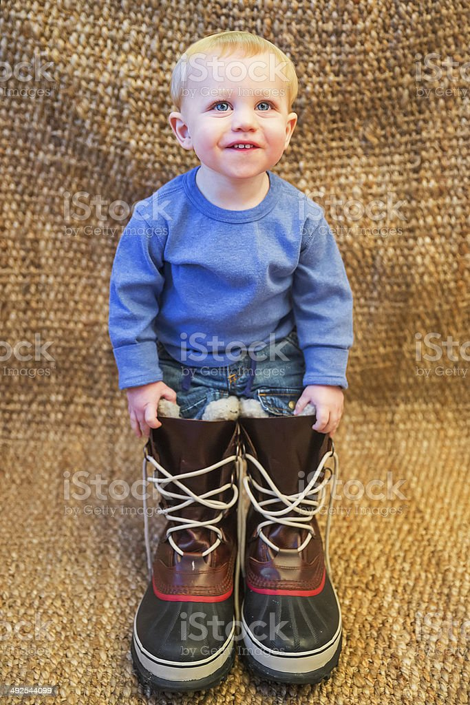 Smiling toddler stands in large snowboots stock photo