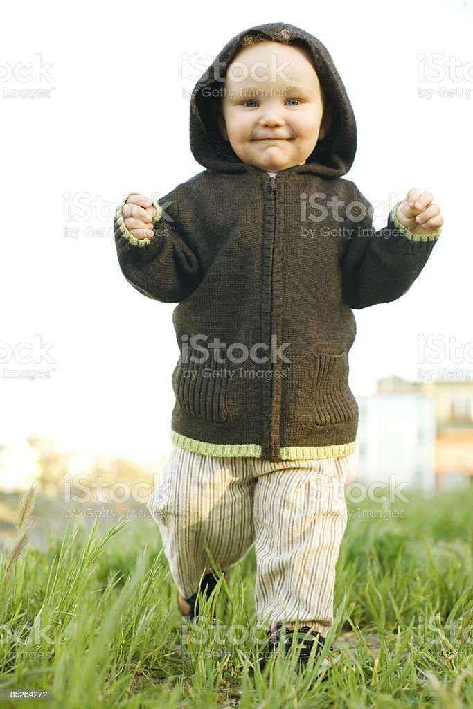 smiling toddler waling in tall grass royalty-free stock photo