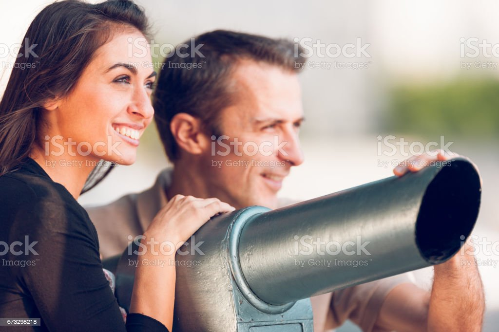 Smiling tourist couple in their holidays using lookout binoculars royalty-free stock photo