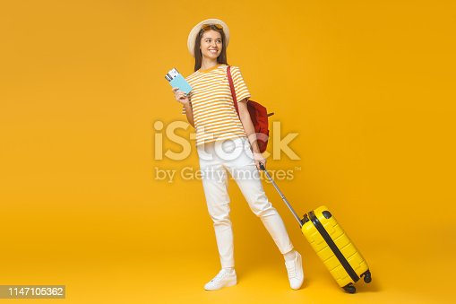 Smiling tourist girl standing with suitcase and backpack, isolated on yellow background. Travel concept