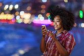 istock Smiling tourist using smart phone at night on street 819770834