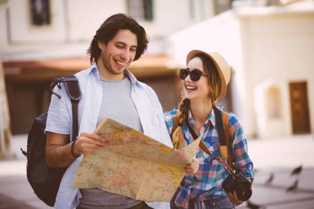 lächelnde touristen auf der suche auf karte in der altstadt - hochzeitsreise zypern stock-fotos und bilder