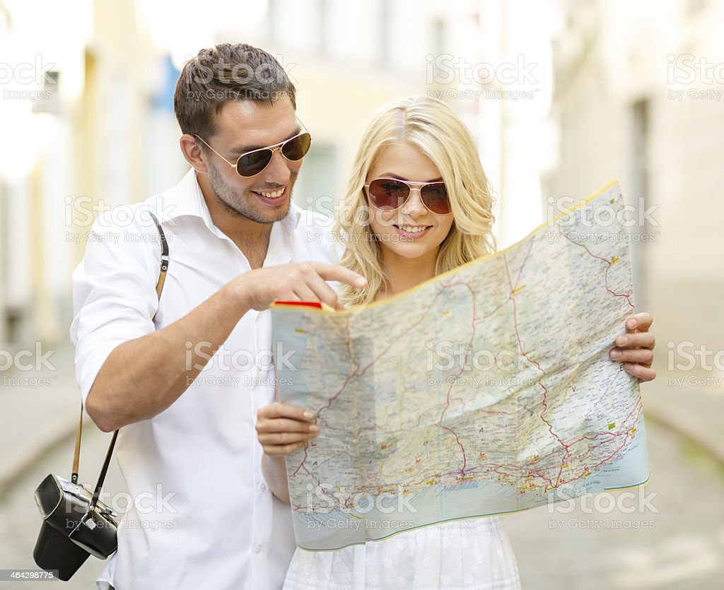 Smiling tourists studying map of city stock photo
