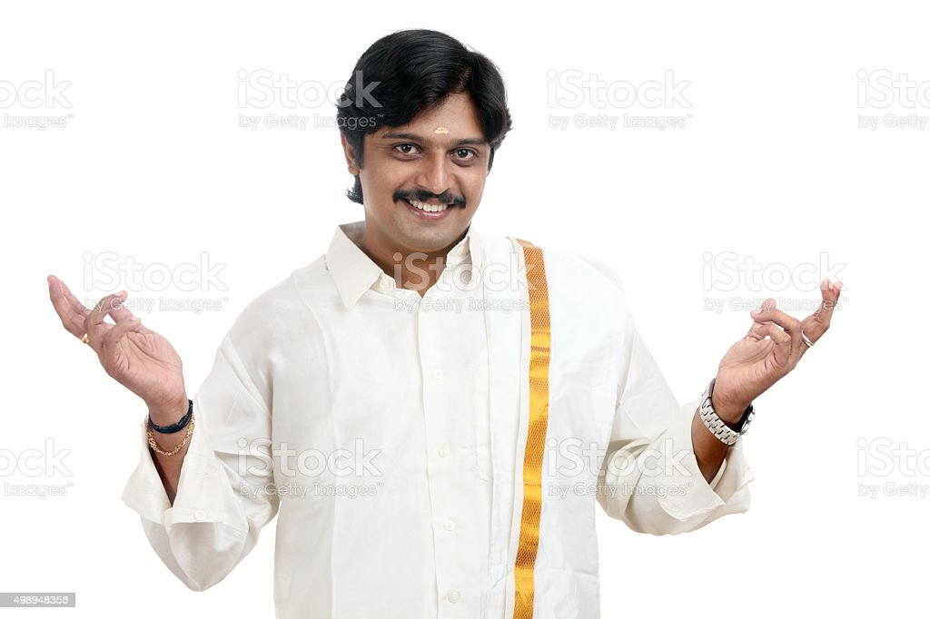 Smiling traditional Indian young man gesturing stock photo