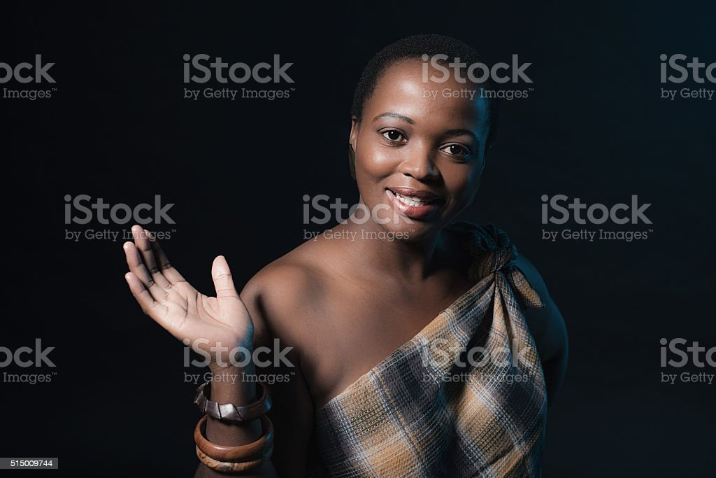 Smiling traditional xhosa woman wearing brown fabric and bracelets. stock photo