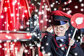 Little child boy in winter as nostalgic railroad conductor beside large wheels of a steam locomotive with snowflakes and copy space