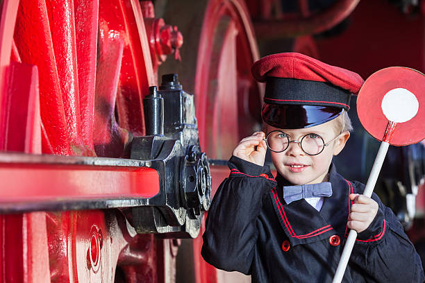 smiling train conductor boy - transport conductor stock photos and pictures