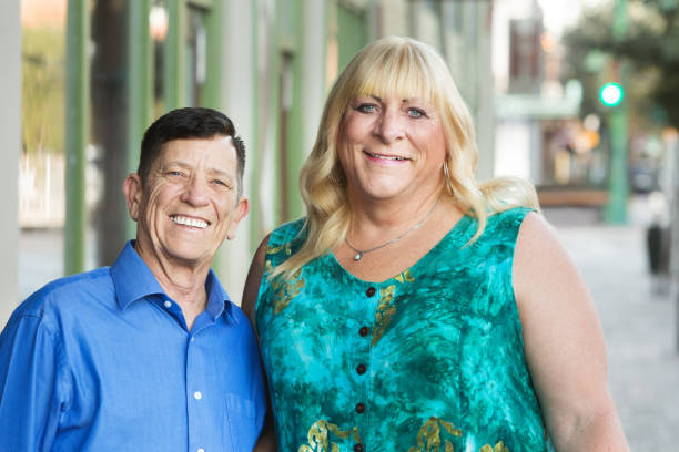 Smiling transgender male and female friends Smiling mature transgender friends standing together outside in urban setting transgender stock pictures, royalty-free photos & images