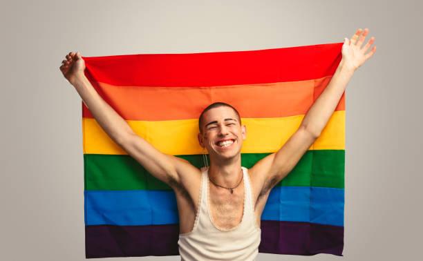 """誇り旗を持つ笑顔のトランスジェンダーの男 - """"gender fluid"""" ストックフォトと画像"""