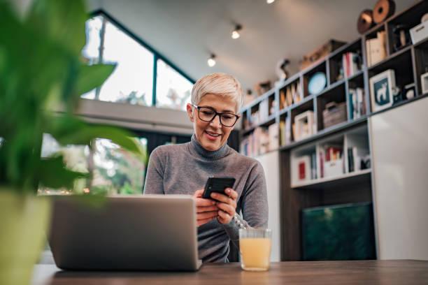 Sonriendo mujer mayor de moda usando el teléfono inteligente en la oficina en casa, retrato. - foto de stock