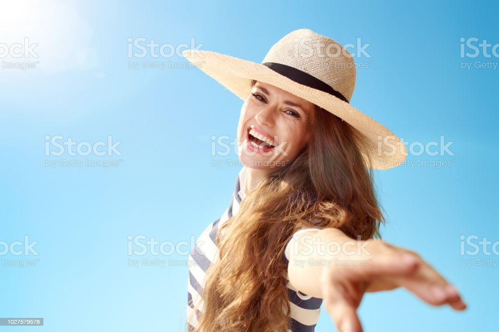 Portrait of smiling trendy woman in straw hat having fun time against...