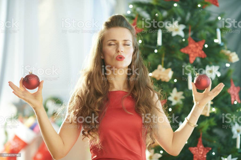 smiling trendy woman near Christmas tree doing yoga smiling trendy woman in red dress near Christmas tree doing yoga Adult Stock Photo
