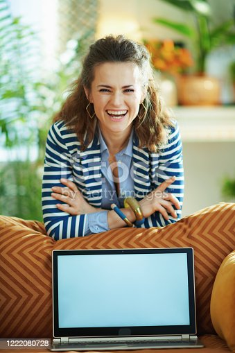 Portrait of smiling trendy 40 years old woman in blue blouse and striped jacket at modern home in sunny day near couch showing laptop blank screen.