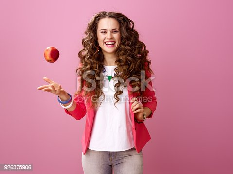 istock smiling trendy woman on pink background throwing up an apple 926375906