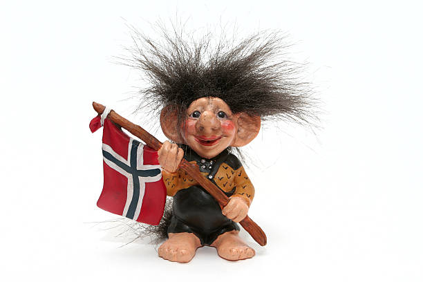 A smiling troll doll with wild hair holds the flag of Norway figurine of smiling troll hanging a flag at his arms isolated on a white, norway norwegian culture stock pictures, royalty-free photos & images